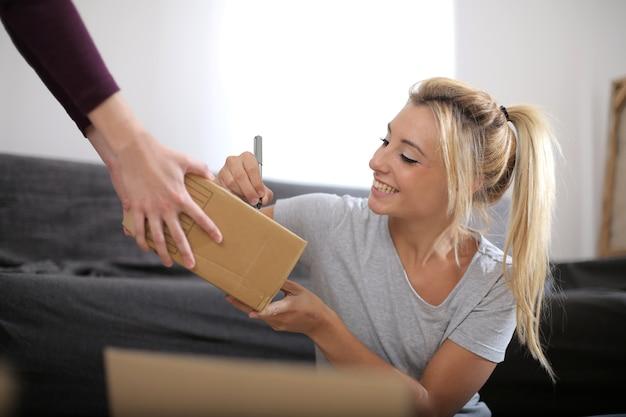 상자로 둘러싸인 골판지 상자에 아름다운 백인 여성 쓰기보기