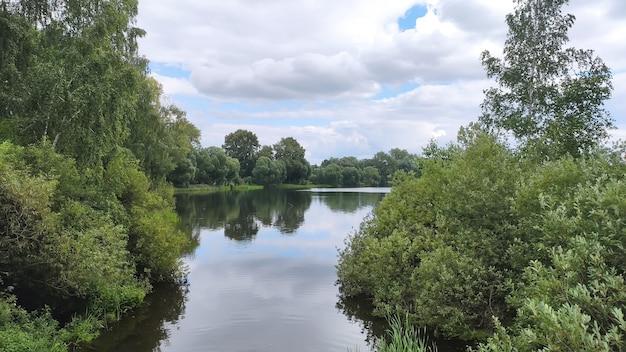 Вид на красивое озеро в лесу среди зеленых деревьев с красивым отражением летом.