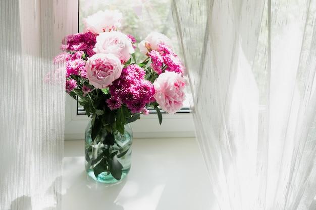 窓の花瓶にピンクの牡丹と菊の花束のビュー。コンセプトの背景、花、休日。