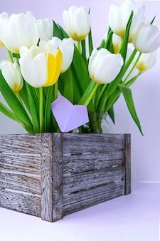 木製の箱に立っている白いチューリップの花束のビュー