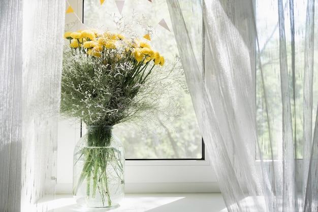 窓の花瓶に黄色い菊の花束のビュー。コンセプトの背景、花、休日。