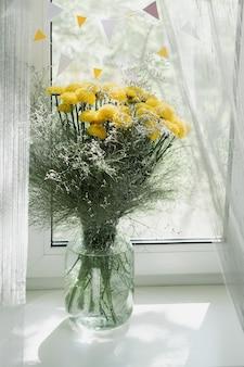 窓の花瓶に黄色い菊の花束のビュー。コンセプトの背景、花、休日。 Premium写真