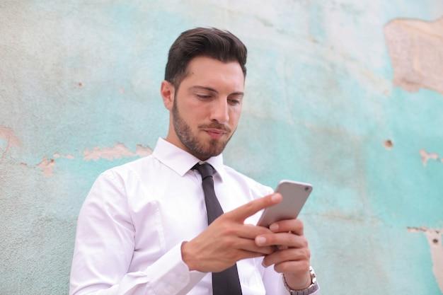 緑の壁の前に立っている間彼の電話で遊んでいる白人男性のビュー