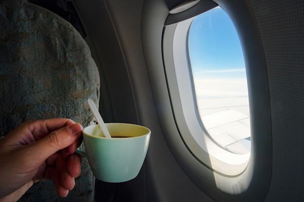 Вид на чашку кофе, держащуюся рукой человека перед окном самолета в полете на самолете.