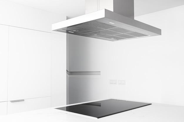 Вид вытяжки и электрической плиты современной и минималистской кухни