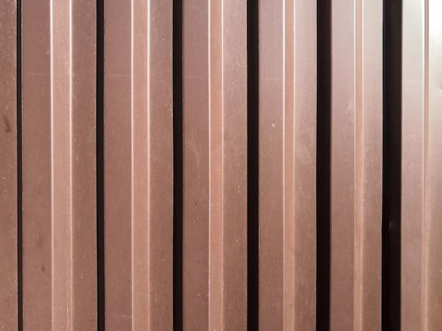 明るい日光の下で横から照らされた垂直波のある波形の茶色の鉄板のビュー