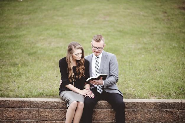 庭で一緒に本を読んでいる間、フォーマルな服を着ているカップルのビュー