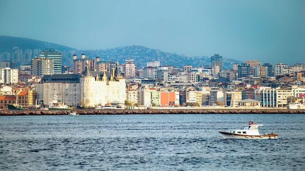Вид на район с жилыми и высокими современными зданиями в стамбуле, пролив босфор с движущейся лодкой на переднем плане, турция
