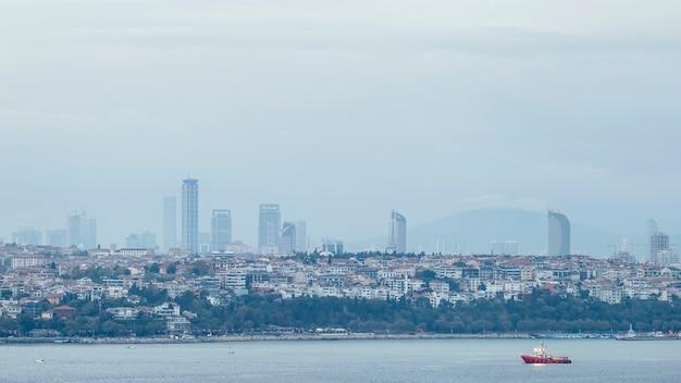 イスタンブール、ボスポラス海峡、前景に移動する船、トルコの住宅と高度な近代的な建物のある地区のビュー