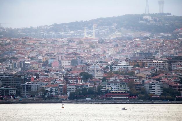 イスタンブール、ボスポラス海峡、前景に移動ボート、トルコの住宅とモスクのある地区のビュー