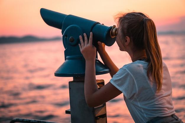 望遠鏡を使用して、桟橋からビーチに沈む夕日を見ている女性のビュー