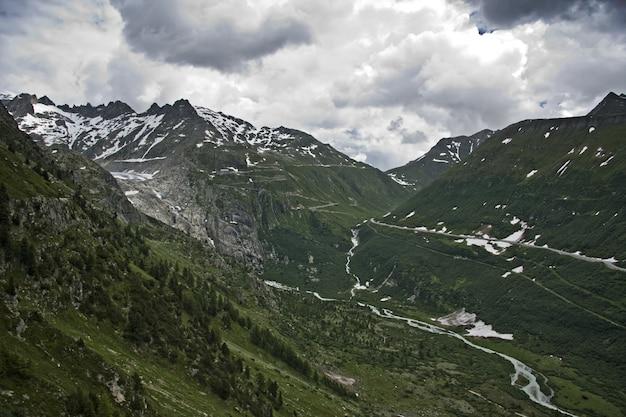 Вид на замерзшую реку в окружении зеленых гор под пасмурным небом