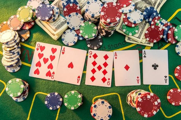 많은 포커 카드와 칩 녹색 매트가있는 게임 테이블보기