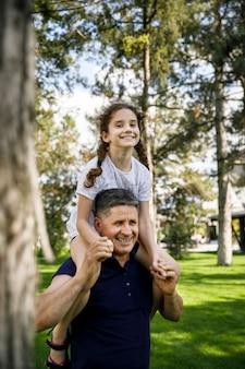姪っ子を肩に抱えた祖父の姿は、自然の中で一緒に楽しい一日を楽しんでいます。垂直方向のビュー。