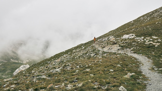 山の間の小道を歩いているハイカーの眺め
