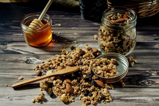 Вид на банку с мюсли, натуральный пчелиный мед и мюсли, миндаль и сухофрукты на деревянном столе с ложкой. концепция здорового и естественного питания.