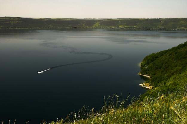 大きな湖や川を高い角度から見たところ。遠くからモーターボートがジグザグに航行しているのを見ることができます。