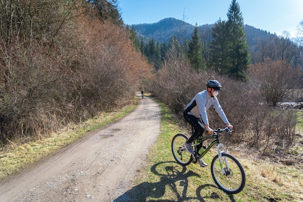 코로나 바이러스 격리 기간 동안 나무에 둘러싸인 도로에서 자전거를 타는 남성의 모습