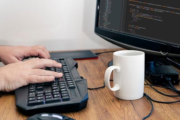 작업하는 동안 집 책상에서 pc나 컴퓨터 키보드로 타이핑하는 남자의 손 보기