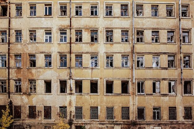 깨진 창문이있는 다층 버려진 집의 전망.