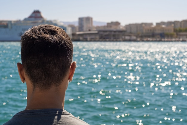 Взгляд подростка в порту малаги, смотрящего на море.