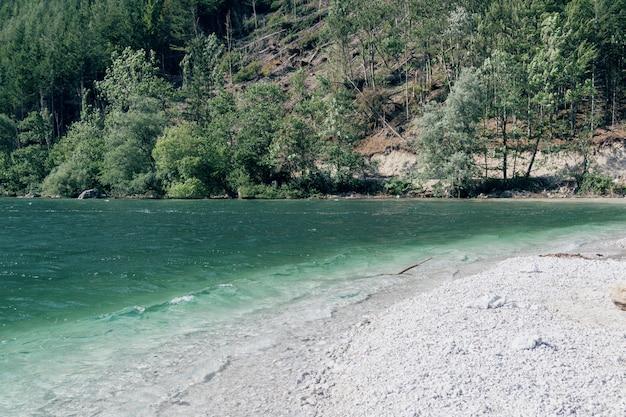 ターコイズブルーの色の水、崖、森と白い小石の山の湖と野生のビーチの眺め。自然、山、トラック、旅行の概念。