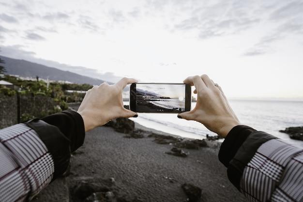 海の彼の電話を通して写真を撮っている女性のビュー