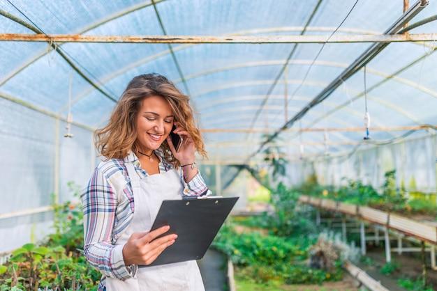 スマートフォンを使用して植物の保育園で働く若い魅力的な女性の眺め