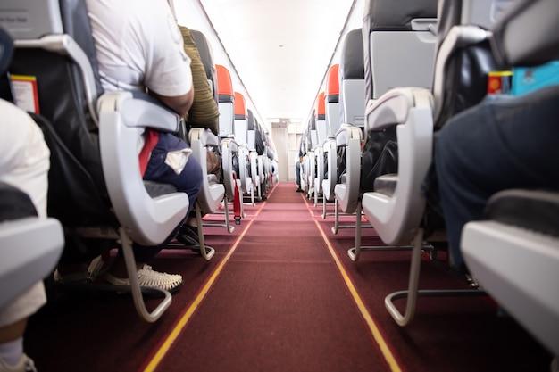 乗客が座席に座っている飛行機の通路のビュー