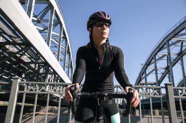 橋を背景にポーズをとる自転車を持つアスリートのビュー
