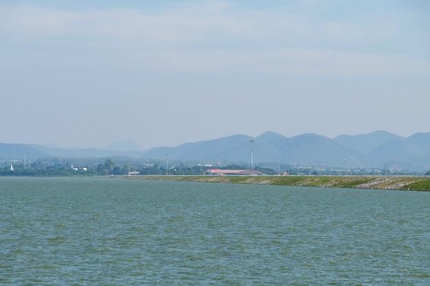 Вид на асфальтированную дорогу на гребне плотины большого водохранилища, расположенного на равнине между горными хребтами, вид спереди для копии пространства.