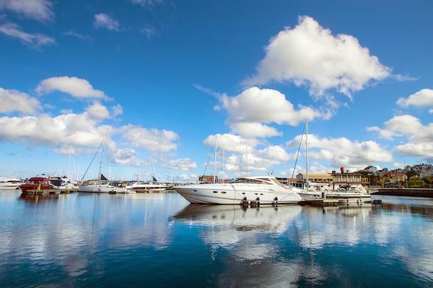 Вид на залив утром в маленьком шведском городке, швеция. дома и корабли на фоне неба