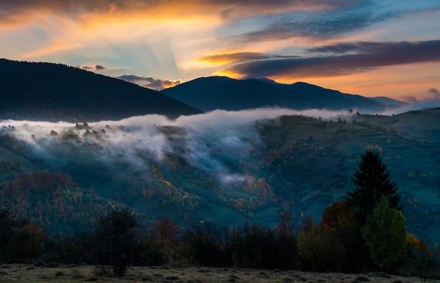 丘の中腹の牧草地の上の美しい曇り空の眺め。煙と劇的な明るい空を背景にした山々の雄大な風景。自然と夜明けの概念。