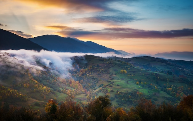 Вид красивого облачного неба над лугом на склоне холма. величественный пейзаж гор с дымом и драматическим ярким небом на фоне. понятие о природе и рассвете.