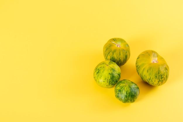 黄色の背景に美しい緑のゼブラトマトのビュー
