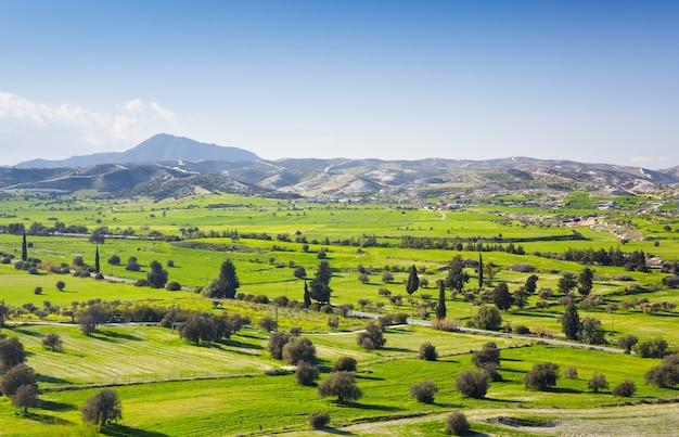 푸른 하늘과 봄 날에 구름 화창한 날에 백그라운드에서 신선한 녹색 초원과 눈 덮힌 산 꼭대기와 아름 다운 풍경의 전망.