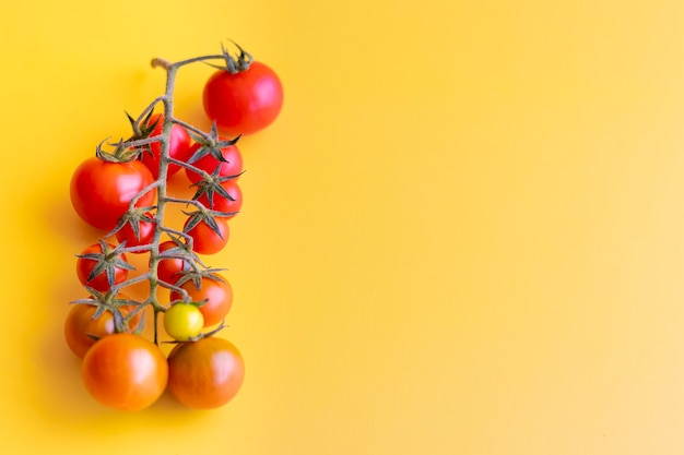 黄色の背景に美しい赤いチェリートマトのビュー