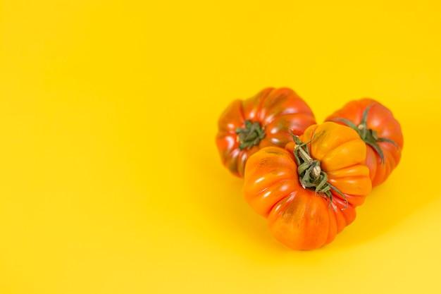 黄色の背景に美しい赤い家宝のトマトのビュー