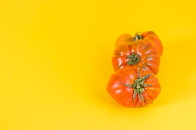 Вид красивых красных помидоров семейной реликвии на желтом