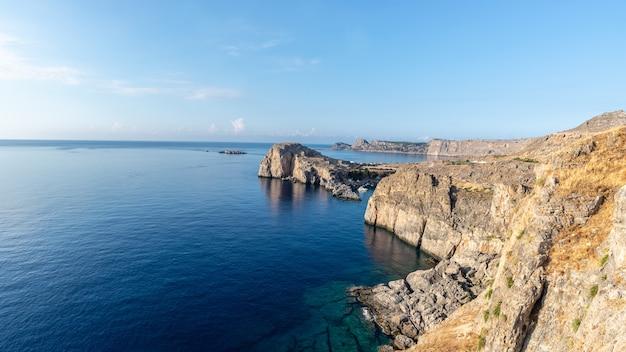 Вид на красивые скалистые утесы острова родос, уходящий в голубое море.