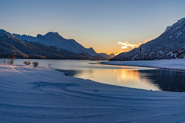 Вид на красивый солнечный свет на озере сильваплана, швейцария, в холодный зимний вечер со снегом на переднем плане и фоном горного хребта