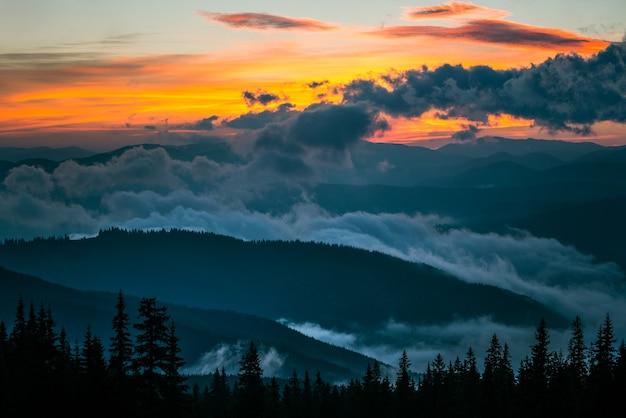 山の谷の美しい夕日の眺め。背景に劇的な空と雲に囲まれた丘。自然の美しさと日没の概念。