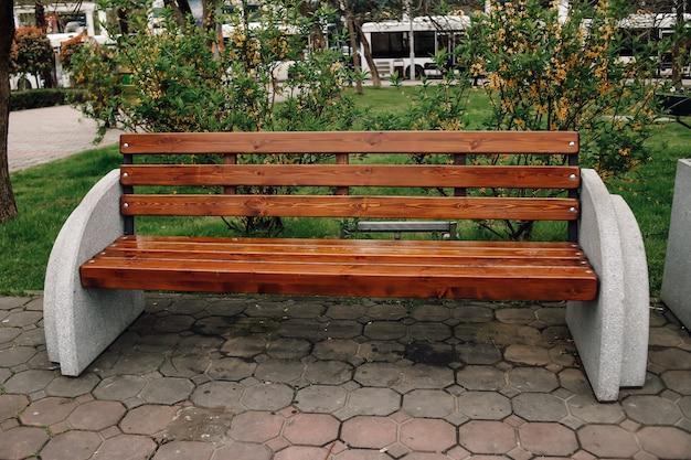 덤불, 야자수와 마을의 식물이있는 공공 공원에서 벤치의 전망.