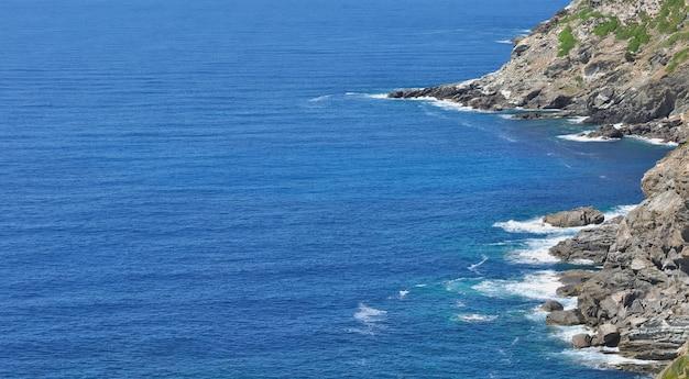 Вид на синее море на скалистых берегах острова корсика во франции