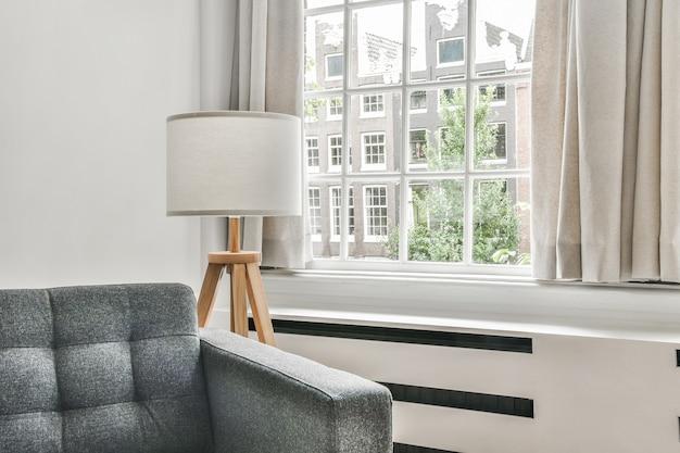 Вид на светлую гостиную с диваном и лампой у окна