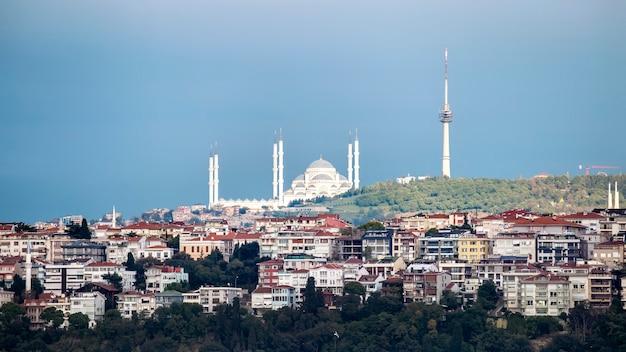 手前に住宅の建物、丘の上の塔、曇りの天気、イスタンブール、トルコと丘の上に位置するカムリカモスクのビュー