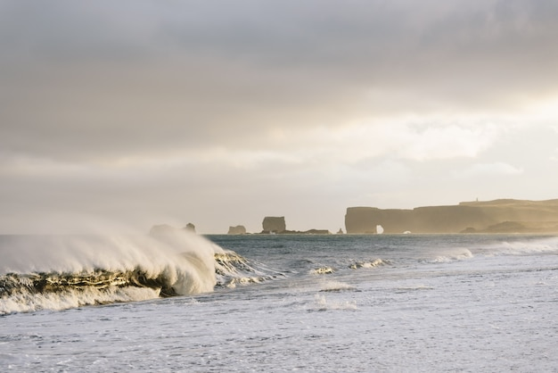 Вид на мыс дирхолей с пляжа рейнисфьяра, исландия. большие волны в океане. штормовая погода с сильным ветром. прекрасный вечерний солнечный свет