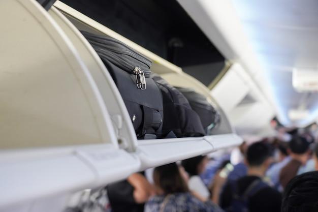 飛行機のキャビンの頭上棚に荷物を運ぶのビュー