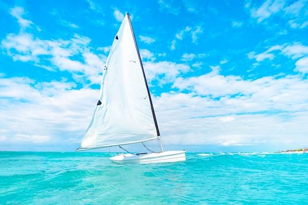 Вид катамарана в открытой воде океана. катамаран с белым парусом дрейфует по бирюзовым водам карибского моря без людей. прекрасный пейзаж.
