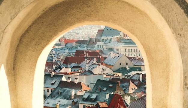 Вид на чески-крумлов зимой из окна, чешская республика. вид на заснеженные красные крыши. путешествия и отдых в европе. рождество и новый год. солнечный зимний день в европейском городе.